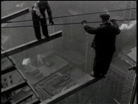 Newsreel / No audio /Workers put top beam on tallest building in New York City / Two workers stand on exposed beams far above the city streets / The...
