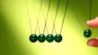 Newton's cradle of green balls
