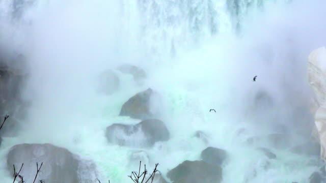 Niagara falls: horseshoe waterfall at the end of the Winter season, water falling on rocks