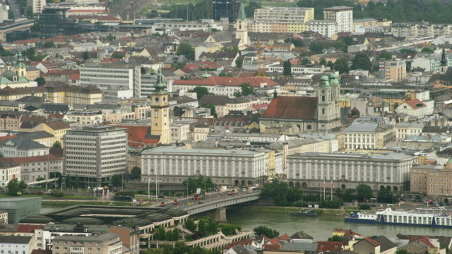 LS TU HA Nibelungenbruecke spanning Danube river, city center with Alter Dom (Old Cathedral) and Stadtpfarrkirche to industrial area with steel and petrochemical plants