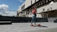 Nice young girl riding skateboard outdoors, slow motion