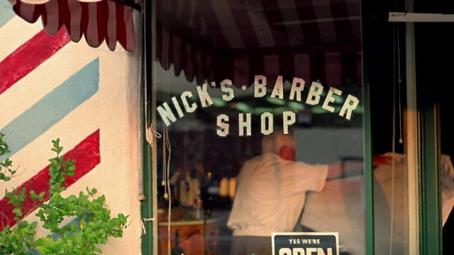 Medium shot Nick's Barber Shop window sign outdoors with barber cleaning up inside