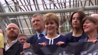 Nicola Sturgeon Willie Rennie and Kezia Dugdale standing with protesters to protest against the controversial 'rape clause'