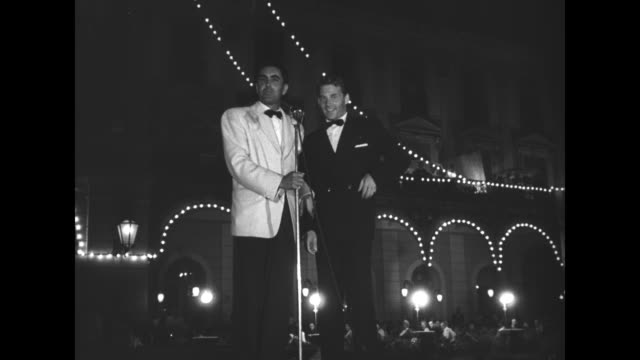 actor Tyrone Power stands with French actor JeanPierre Aumont at a microphone during the Cannes Film Festival's opening party at the Grand Hotel