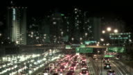 Traffico della città di notte con edifici in sfondo Sfocato