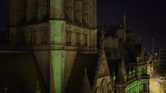 Night Drone footage. Manchester Town Hall at night lit up green. With Mount Street in background