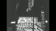 exterior of Palace Theatre with marquee touting the film premiere of 'I Confess' / actress Anne Baxter walks toward theater with director Alfred...