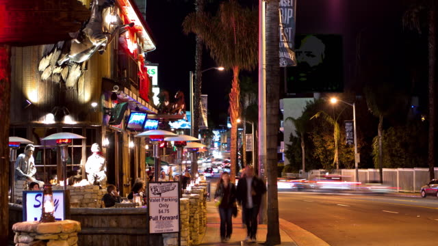 MS T/L night exterior sidewalk dining on Sunset Strip at rustic western-themed steak house restaurant with propane patio heaters as tourists pass by and traffic in background and valet parking sign in foreground