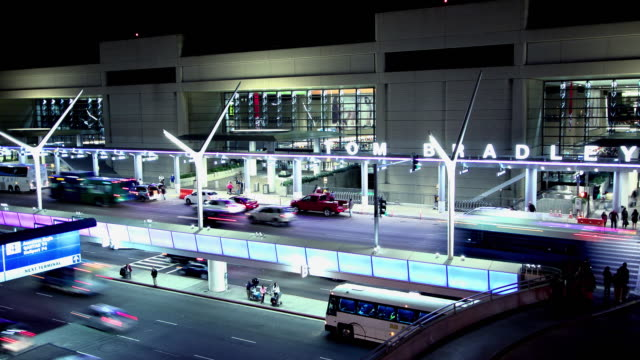 HA T/L night exterior Tom Bradley International Terminal at Los Angeles Airport with buses and shuttles and cars entering and exiting lower level for arrivals and upper level for departures / Los Angeles, California, USA