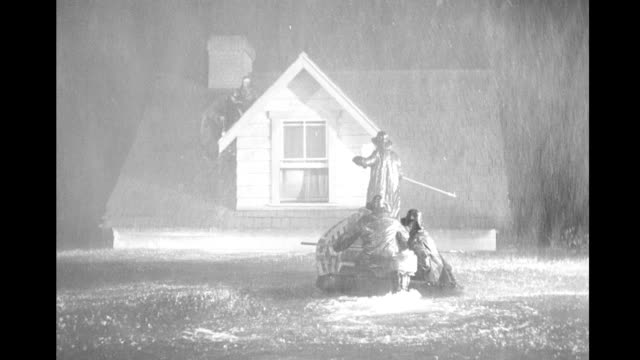 Night heavy rain couple stranded on house roof rescued by men in motorboat Flood couple stranded on roof rescued on January 01 1948 in California
