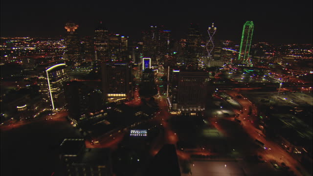 Night low altitude approach toward blue-lit Hunt Oil Bldg then climb over other buildings of downtown Dallas