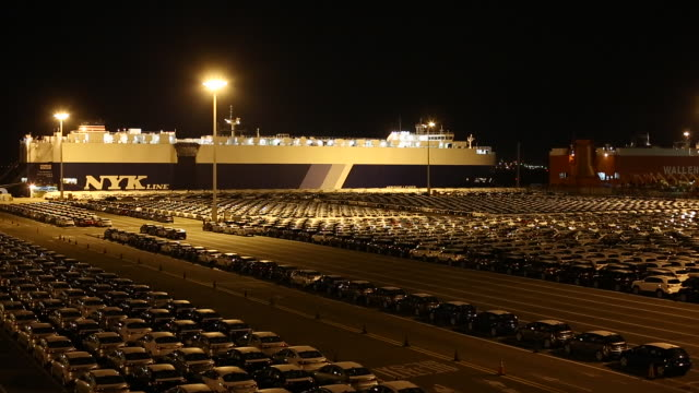 Night scenery of large group of cars at the parking lot near export pier