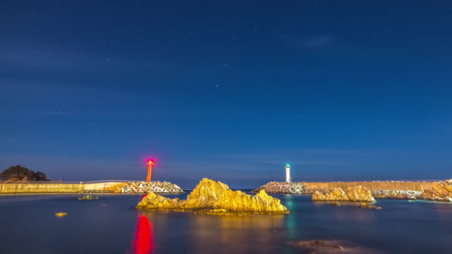 Night scenery of star field and two lighthouses at the sea