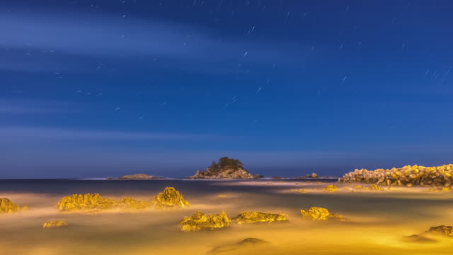 Night scenery of star trail and boulder at the sea