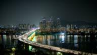 Night Scenery of traffic moving on Cheongdamdaegyo bridge and Skyscraper at Han river