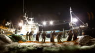 Night Scenery of working fisherman and fisherwoman with fishing net in front of fishing boat at Harbor