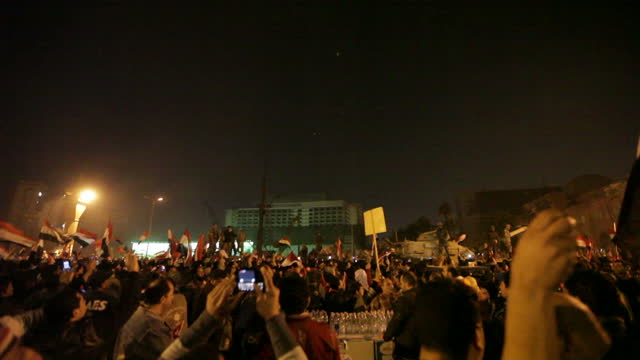 Night shots of protesters marching in crowds of thousands through Tahrir Square calling for President Mubarak to step down on February 11 2011 in...