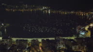 Night skyline over the water at Ipanema Beach in Rio de Janeiro framed with foliage