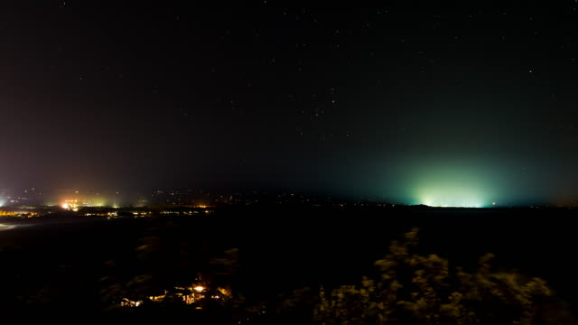 Night timelapse at Byron Bay with stars and the lights of the town, New South Wales, Australia in 4K