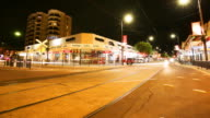 Night timelapse Corner of Jetty Road and Colley Terrace Glenelg looking towards lit up Oasis Deli with Colley Court apartment building behind Streets...
