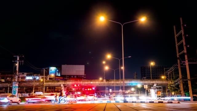 Nachtverkehr um eine Kreuzung und urbanes Leben in der Stadt, Bangkok, Thailand