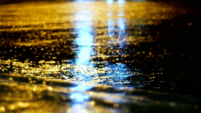 Night traffic light reflect on water surface in rainy day
