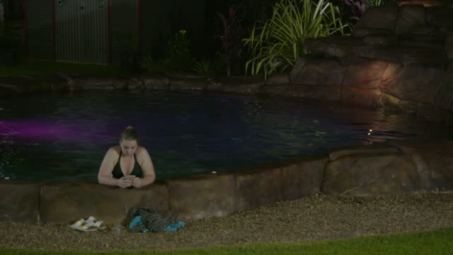 night woman stands in backyard swimming pool water texting on mobile phone as leans against side of pool