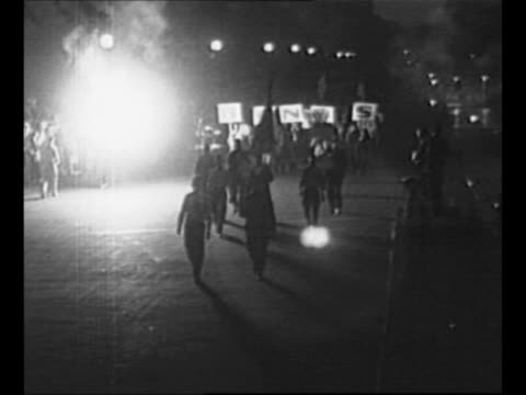 WWI veterans march on Washington DC street holding signs that spell 'BONUS' small fire burns in background / montage Herbert Hoover sits at table in...