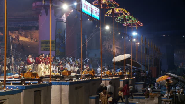 Nighttime shot of a busy wharf and lit ceremony area in a city in India.