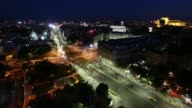 A nighttime timelapse sequence shows high angle skyline view traffic with illuminated headlights driving around the University roundabout in the...