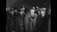Nighttime view of a crowd in fog / SOT Civil Defense Director Arthur W Wallander Sr stands before microphone 'If you are seated in this theater at...