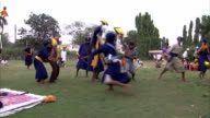 Nihang warriors swing swords and leap in training for battle.