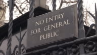 A 'No Entry For General Public' sign hangs on a House of Parliament gate. Available in HD.