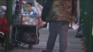 No face tight shot of homeless man walking in street seated alongside shopping cart