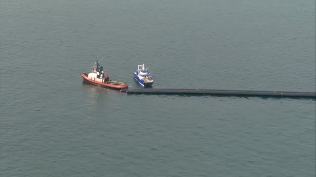 Aerials of giant pipe recovery on Norfolk beach AIR VIEWS of salvage vessel towing giant pipe away from beach