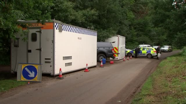 Crime scene general views GVs police at scene police cars and cordons in forest