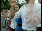 North Korean citizens demonstrate and march shaking fists in unison demanding unification of Korean peninsula following death of leader Kim Il Sung...
