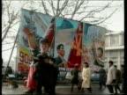 North Korean citizens walk on street past military guards and propaganda posters Pyongyang Dec 93