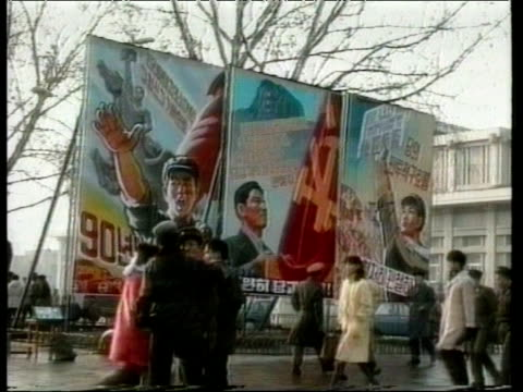 North Korean citizens walk on street past military guards and propaganda posters Pyongyang Dec 93