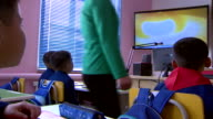 North Korean school children watch a TV in the classroom depicting the detonation of a nucleur bomb