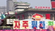 North Korean wellwishers wave flowers as they parade through Pyonyang with a military inspired carnival float