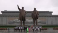 North Koreans bow before the mausoleum of founder Kim Il Sung and his son as the country marks the end of the Korean War which it calls Victory Day
