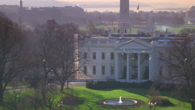 MS North lawn of white house with smoke and birds flying around / Washington D.C., United States