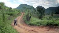 North Thailand Holiday. Man rides moped up steep hill Asia