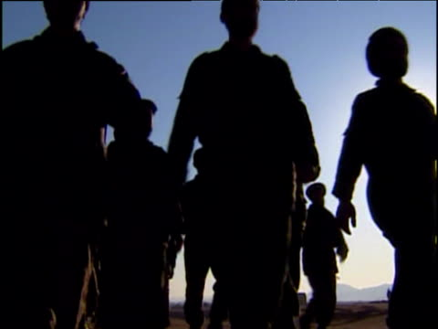 Northern Alliance soldiers march past camera in silhouette War in Afghanistan 2001