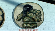 new powersharing government sworn in NORTHERN IRELAND Belfast EXT UDA mural on wall and woman with pushchair past IRA Mural on side of house Traffic...