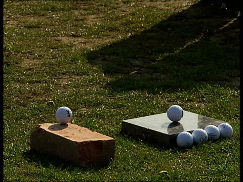 London EXT Ball being struck from driving range tee / Various of golf balls and tees on grass / Various of player striking a golf ball resting on a...