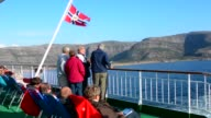 Norway cruise Hurtigruten ship back deck with passengers out enjoying scenes near the Arctic Circle crossing with old classic Norway Postal flag