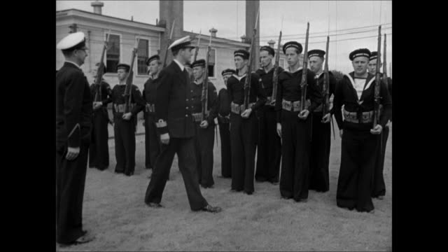 WS Norwegian guard patrolling entrance / MS Recruits in civilian clothing lined up WS British instructor inspecting Norwegian soldiers MS Old sailor...
