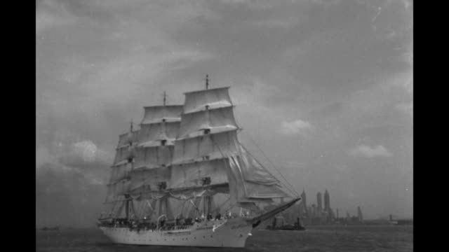 VS Norwegian training ship 'Christian Radich' with sails unfurled and anchor poised as it moves in New York Harbor with New York City skyline and...